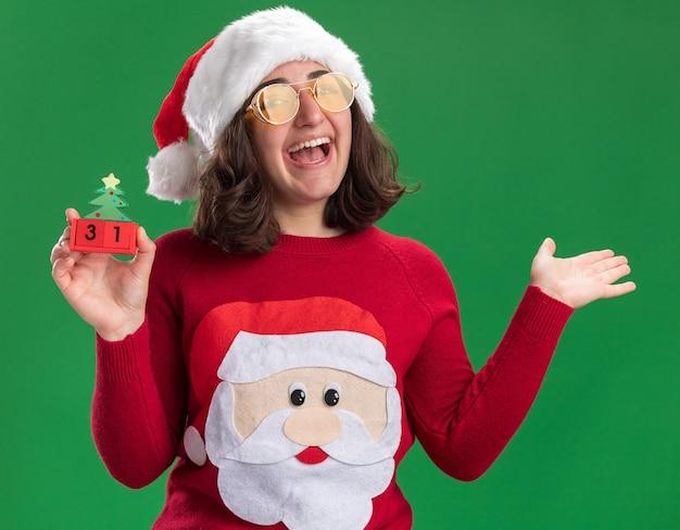 サンタの帽子とメガネを身に着けているクリスマスセーターの少女は、緑の壁の上に立っている腕を上げて幸せで楽しい笑顔で新年の日付とおもちゃの立方体を保持しています