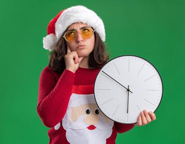 산타 모자와 녹색 배경 위에 의아해 서 찾고 벽 시계를 들고 안경을 쓰고 크리스마스 스웨터에 어린 소녀