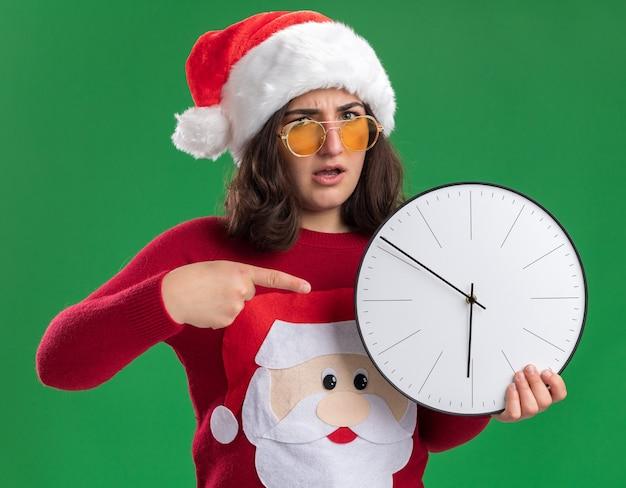 산타 모자와 녹색 배경 위에 서 심각한 얼굴로 카메라를보고 그것에 검지 손가락으로 가리키는 벽 시계를 들고 안경을 쓰고 크리스마스 스웨터에 어린 소녀