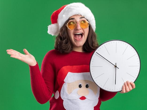 Молодая девушка в рождественском свитере в шляпе санта-клауса и очках смотрит вверх счастливой и взволнованной, держа настенные часы над зеленой стеной