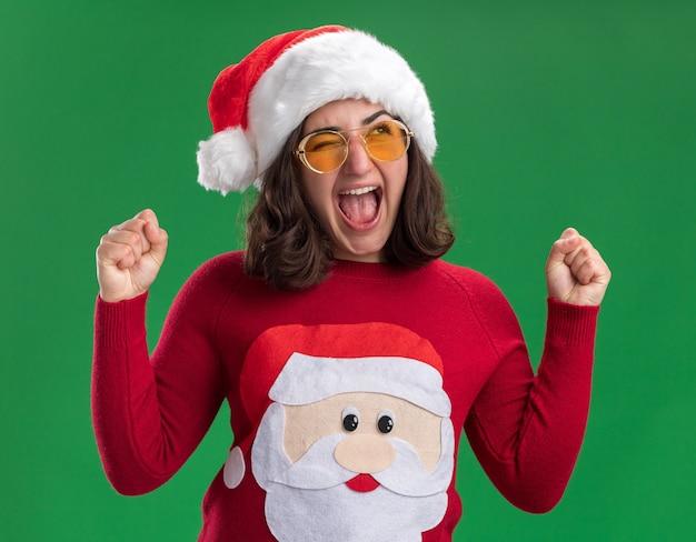 Молодая девушка в рождественском свитере в новогодней шапке и очках кричит взволнованно и безумно счастливо, сжимая кулаки, стоя над зеленой стеной