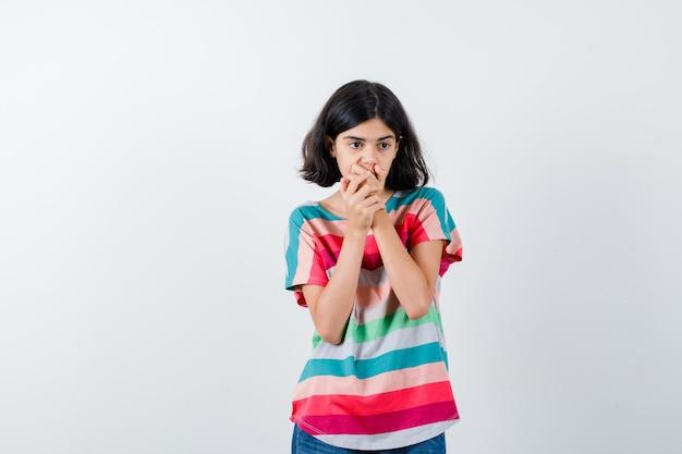 화려한 줄무늬 티셔츠를 입은 어린 소녀가 손으로 입을 가리고 놀란 표정을 하고 있습니다.