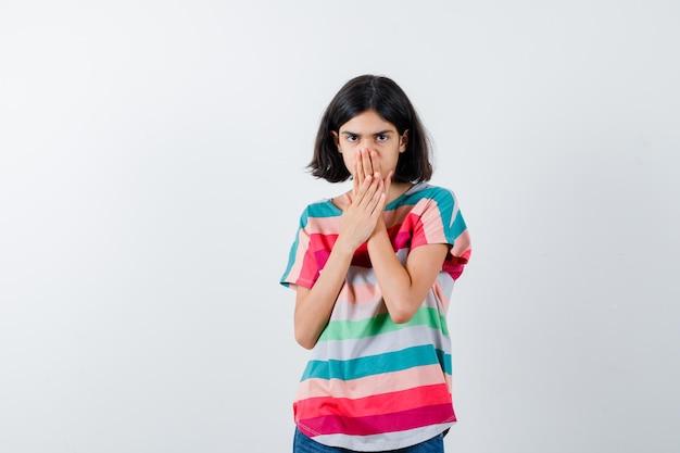 화려한 줄무늬 티셔츠를 입은 어린 소녀가 손으로 입을 가리고 소심한 표정을 짓고 있습니다.