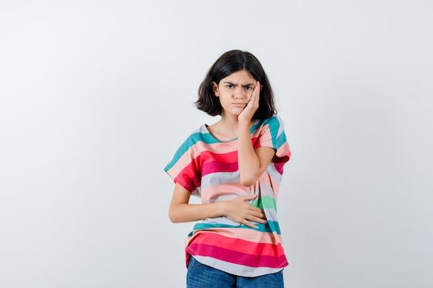歯痛があり、イライラして見えるカラフルなストライプのtシャツの少女、正面図。