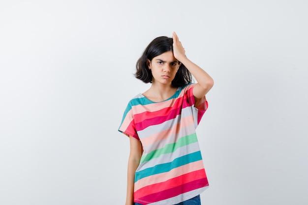 Молодая девушка в красочной полосатой футболке держит руку на голове и выглядит раздраженной, вид спереди.