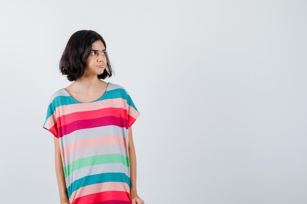 カラフルなストライプのtシャツを着た少女がポーズをとってかわいい、正面を見て目をそらします。