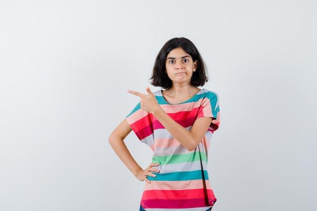カラフルなストライプのtシャツを着た少女が人差し指で左を指して腰に手を握り、真面目な正面図を見てください。