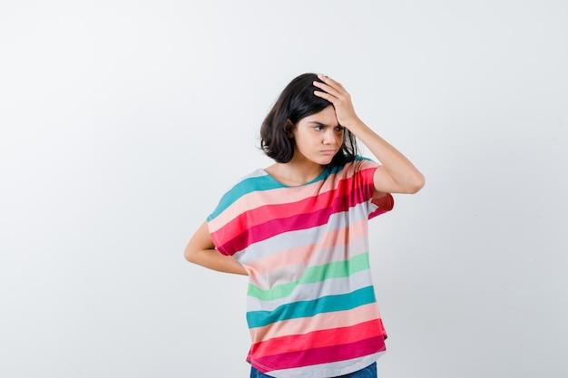 Молодая девушка в красочной полосатой футболке положила руку на лоб, держа одну руку за талию и выглядела раздраженной, вид спереди.
