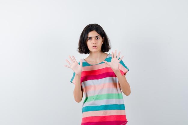 カラフルなストライプのtシャツを着た少女は、降伏のジェスチャーで手のひらを上げ、ショックを受けた、正面図を探しています。