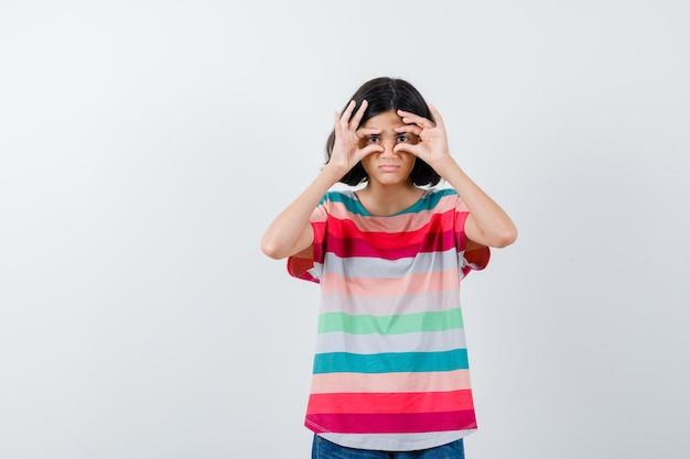 Молодая девушка в красочной полосатой футболке показывает жест бинокля и выглядит мило, вид спереди.