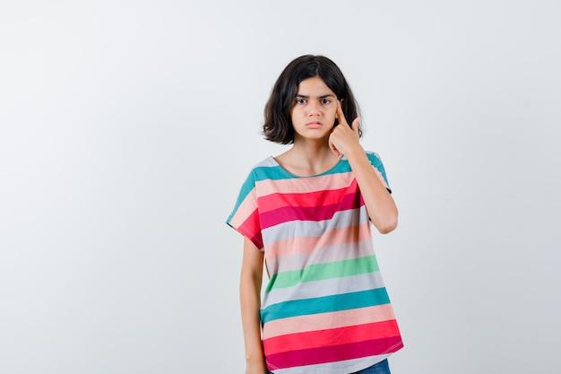カラフルな縞模様のtシャツを着た少女は、頭の近くで銃のジェスチャーを示し、真剣に、正面図を表示します。
