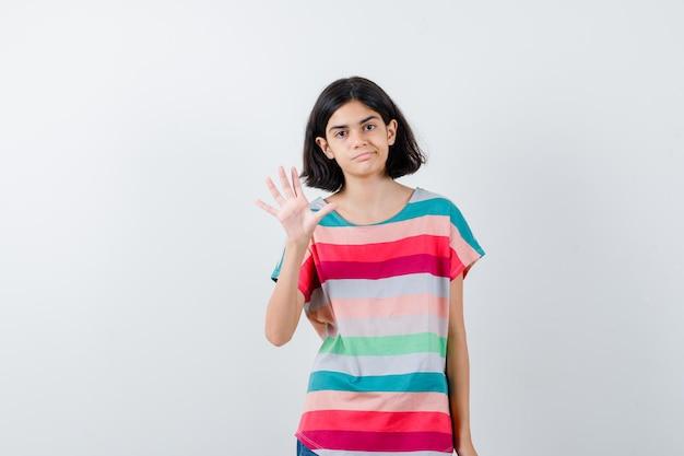 화려한 줄무늬 티셔츠를 입은 어린 소녀가 한 손을 흔들며 인사하며 입술을 구부리고 앞모습이 예뻐 보입니다.