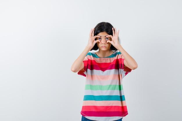 Молодая девушка в красочной полосатой футболке пытается открыть глаза пальцами и выглядит удивленно, вид спереди.