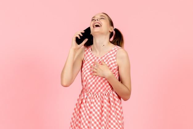 電話で話し、ピンクで笑っているかわいい明るいドレスの少女