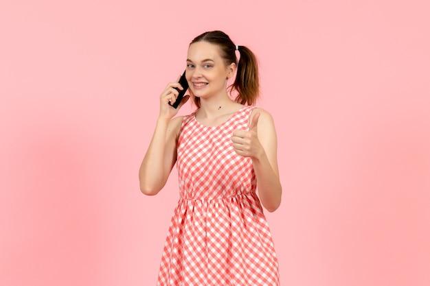ピンクの笑顔で電話で話しているかわいい明るいドレスの少女