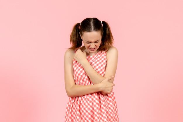 かわいいピンクのドレスを着た少女はピンクで彼女の腕を傷つけます