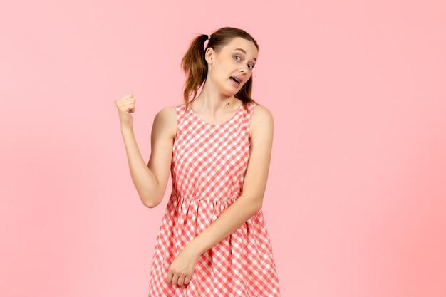 핑크에 가리키는 귀여운 핑크 드레스에 어린 소녀