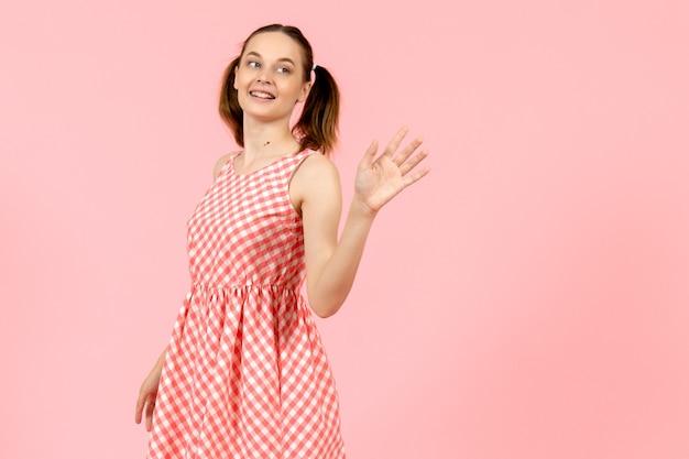 ピンクの笑顔と手を振ってかわいいピンクのドレスの少女
