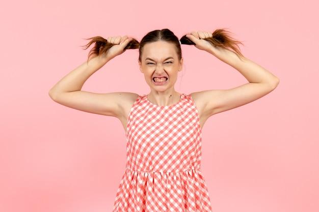 ピンクの怒っている表情とかわいいピンクのドレスの少女