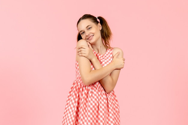 喜んで表情とピンクの笑顔でかわいいピンクのドレスを着た少女