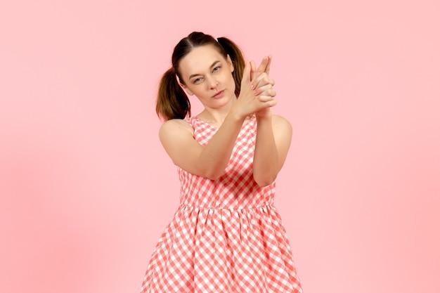 Молодая девушка в милом розовом платье с пистолетом держит позу на розовом