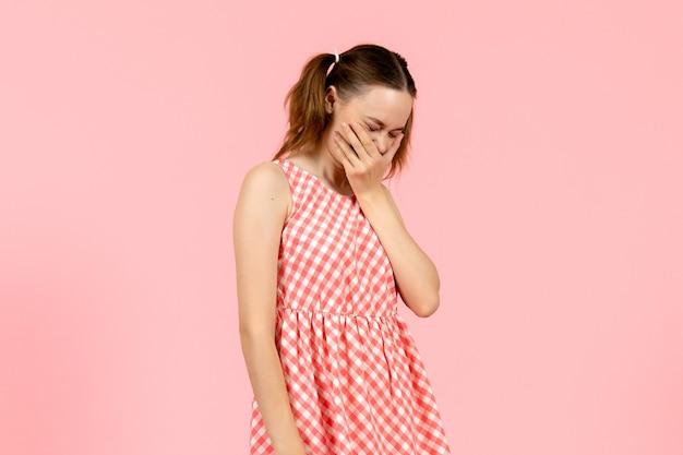 ピンクの笑いの表情とかわいいピンクのドレスの少女