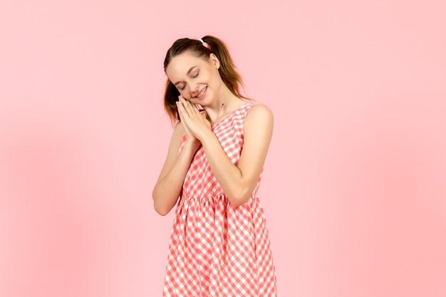 Молодая девушка в милом розовом платье с улыбающимся выражением лица на розовом