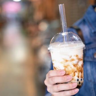デニムジャケットの若い女の子が台湾のナイトマーケットで黒糖風味のタピオカパールバブルミルクティーとガラスストローを飲んでいます、クローズアップ、ボケ