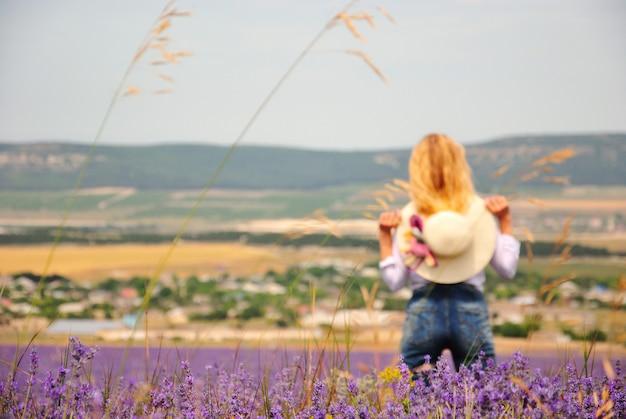 라벤더 밭에서 데님 바지와 흰색 드레스를 입은 어린 소녀