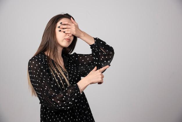Молодая девушка в платье, закрывая глаза руками и указывая в сторону.