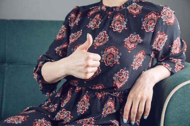 Молодая девушка в платье показывает палец вверх, сидя на диване