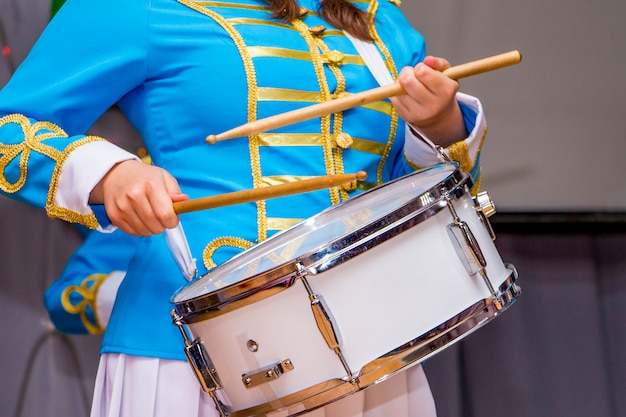 エレガントなスーツの若い女の子がドラムを果たしています。