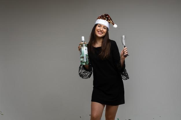 색종이 조각, 복사 공간으로 회색 배경에 휴일을 축하하는 선물과 와인 한 병과 축제 마스크에 어린 소녀