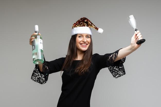Молодая девушка в праздничной маске с подарком и бутылкой вина празднует праздник на сером фоне с конфетти, копией пространства