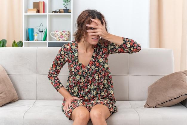 Молодая девушка в цветочном платье закрывает глаза приятелем, глядя сквозь пальцы, сидя на диване в светлой гостиной