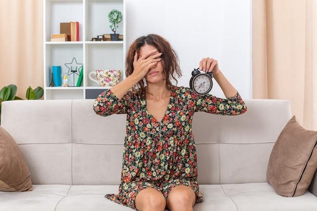 Молодая девушка в цветочном платье держит будильник, прикрывая глаза рукой, уставшей и скучающей, сидя на диване в светлой гостиной