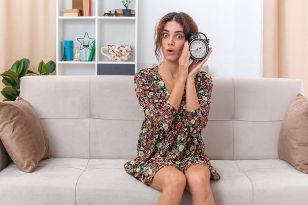 Молодая девушка в цветочном платье держит будильник с удивленным видом, сидя на диване в светлой гостиной