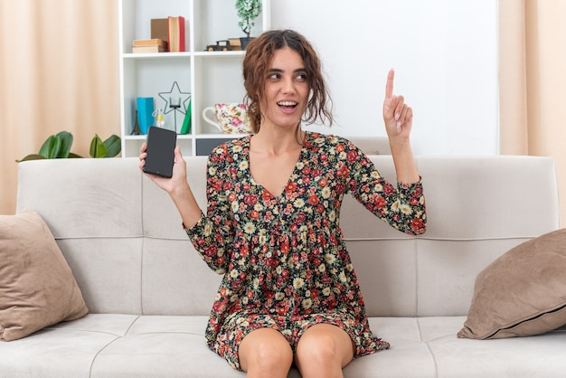 Молодая девушка в цветочном платье, держащая смартфон, выглядит удивленным и счастливым, показывает указательный палец с отличной новой идеей, сидя на диване в светлой гостиной