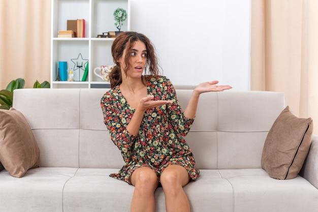 Молодая девушка в цветочном платье смотрит в сторону, смущенная, представляя рукой, сидящей на диване в светлой гостиной