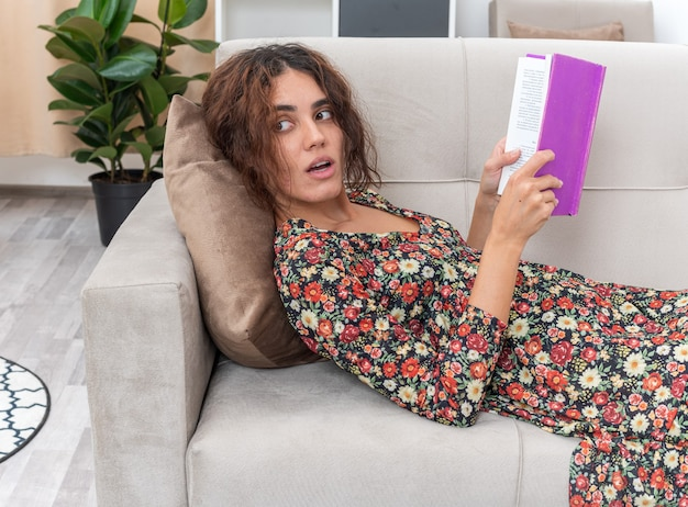 明るいリビング ルームのソファに横になっている家で週末を過ごすリラックスした本を持つ花柄のドレスの若い女の子