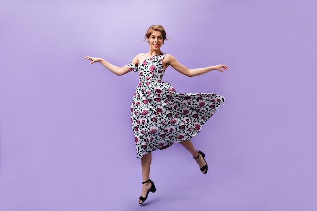 무성한 드레스에 어린 소녀는 보라색 배경에 점프. 격리 된 배경에서 웃 고 다채로운 최신 유행 옷에 사랑스러운 아름 다운 여자.