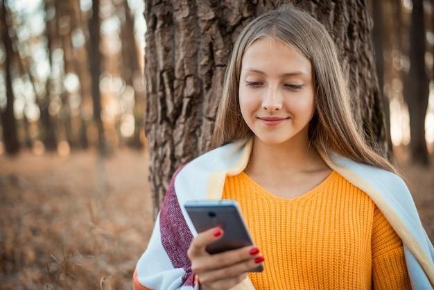 친구들과 소통하는 인터넷 서핑 주위에 밝은 단풍으로 가득한 숲 속의 어린 소녀
