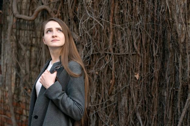 Молодая девушка в строгом костюме на фоне старого деревянного забора. портрет бизнес-леди.