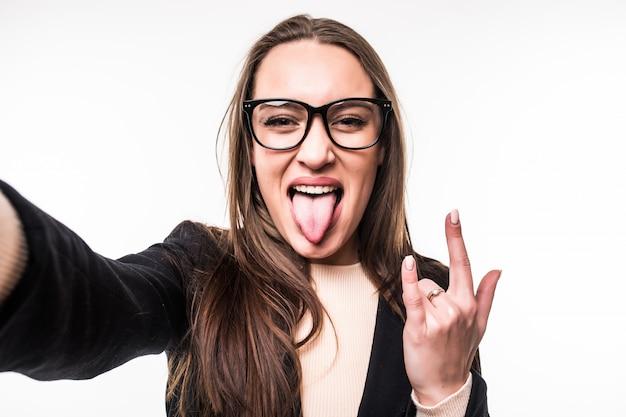 メガネの若い女の子はロックサインと白で隔離される舌を示しています