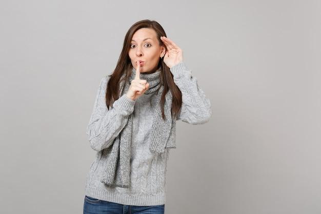 회색 스웨터 스카프를 두른 어린 소녀는 입술에 손가락을 대고 조용히 말하는 쉿 제스처 도청과 회색 배경에 격리된 청력을 말합니다. 건강한 패션 라이프스타일 사람들은 추운 계절 개념을 감정합니다.