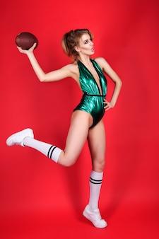 彼の手で笑顔とボールを保持している赤い背景の上の緑の水着の若い女の子