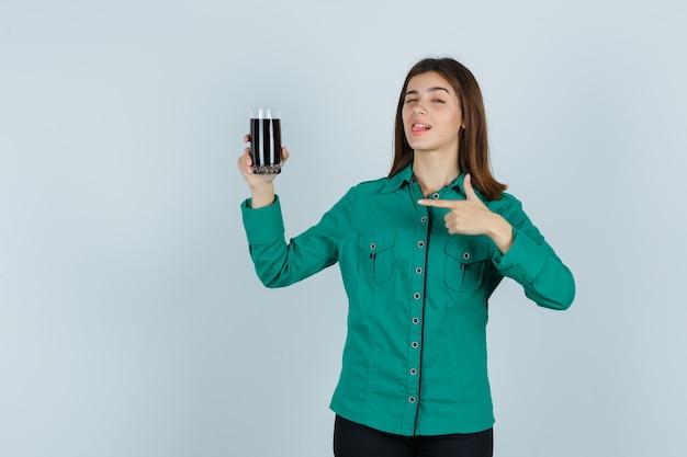 緑のブラウスを着た若い女の子、黒い液体のガラスを保持し、それを指して、まばたきとかわいい、正面図を保持している黒いズボン。