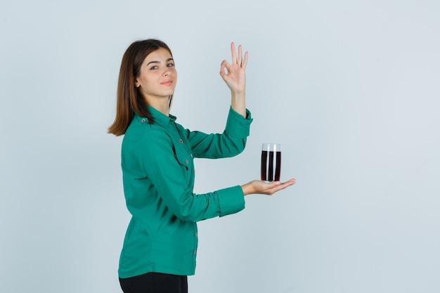 Молодая девушка в зеленой блузке, черных штанах держит стакан с черной жидкостью, показывает знак ок и выглядит весело, вид спереди.