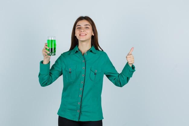緑のブラウス、緑の液体のガラスを保持している黒のズボン、親指を上に表示し、陽気に見える、正面図の若い女の子。