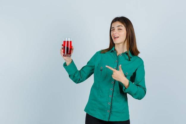 Молодая девушка в зеленой блузке, черных штанах держит стакан с красной жидкостью, указывая на нее, подмигивая и выглядя мило, вид спереди.